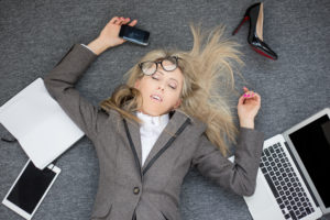 Young overworked business woman sleeping on floor